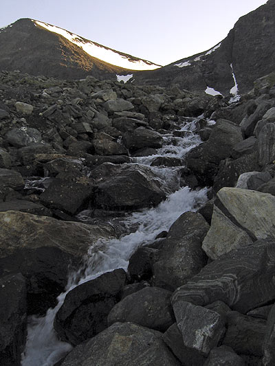 A small brook coming down from a lake with water from melting snow and glaciers